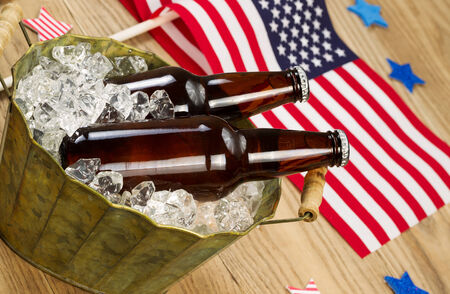 Angled horizontal photo of glass bottled beer in old metal bucket filled with ice and American flags in background for celebration of Independence Day photo