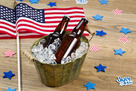 Horizontal photo of glass bottled beer in old metal bucket filled with ice and American flags in background for celebration of Independence Day photo