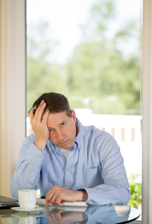 Vertical image of mature man showing depression by holding his head in one hand while working from home with bright daylight coming in from window in background Stock Photo - 29484708