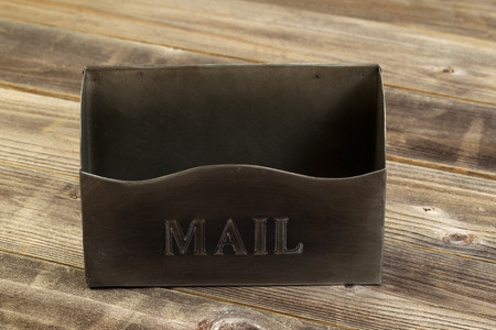 old envelope: Front view of an empty old metal mailbox on rustic wooded boards