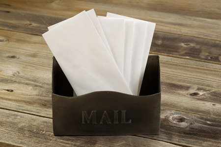 Front view of an old metal mailbox filled with white envelopes on rustic wooded boards photo