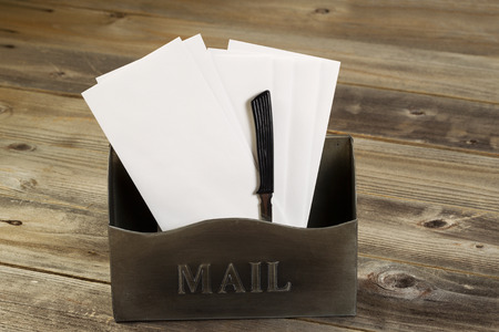Front view of an old metal mailbox filled with white envelopes and letter opener on rustic wooded boards photo