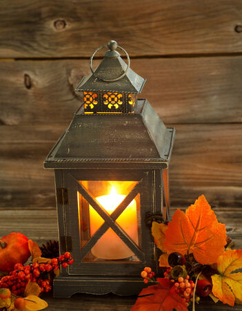 candle holder: Vertical front view of an old Asian design lantern and white candle glowing brightly inside with autumn decorations on rustic wood Stock Photo