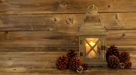 candle holder: Horizontal front view of an old Asian design lantern and white candle glowing brightly inside with natural pine cones decorations on rustic wood