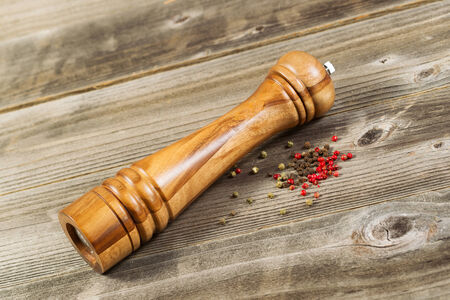 Angled photo of a wooden pepper mill with whole dried peppercorns on rustic wood