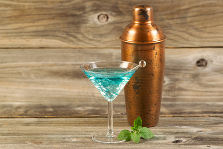 shaken: Horizontal photo of a mixed drink, fresh mint leaves, stir stick and a metal mixer resting on rustic wood