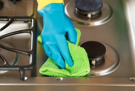 stainless steel range: Closeup horizontal image of hand wearing rubber glove while cleaning stove top range with microfiber rag Stock Photo