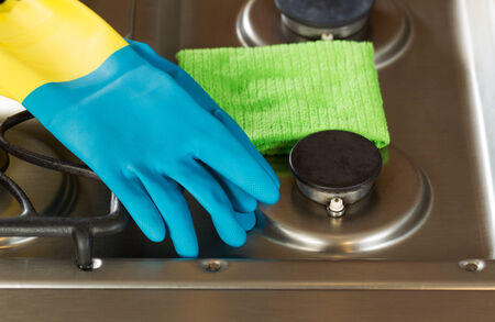 stainless steel range: Closeup horizontal image of rubber gloves and microfiber rag on top of stove top range