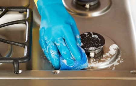 domestic kitchen: Closeup horizontal image of hand wearing rubber glove while cleaning stove top range with soapy sponge  Stock Photo