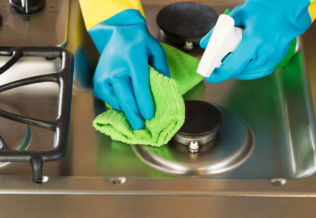Closeup horizontal image of hands wearing rubber gloves while cleaning stove top range with spray bottle and microfiber rag photo