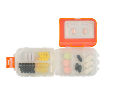 Small plastic medicine container filled with various pills inside isolated on white