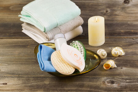 Horizontal front top view of spa hygiene accessories in glass bowl, light white candle with clean stacked towels in background and seashells on rustic wood photo