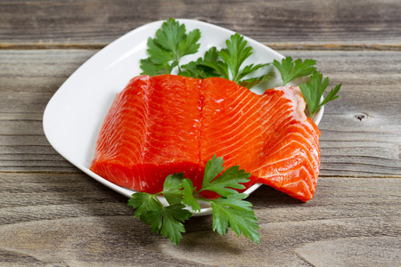 rustic  wood: Closeup horizontal photo of fresh red salmon fillet on white plate with parsley on the side and rustic wood underneath