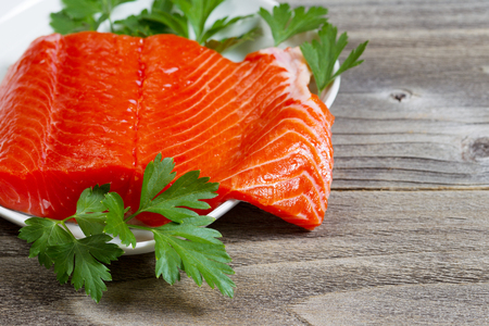 rustic  wood: Closeup horizontal photo of fresh sockeye salmon fillet, partially out of plate, with parsley on the side and rustic wood underneath