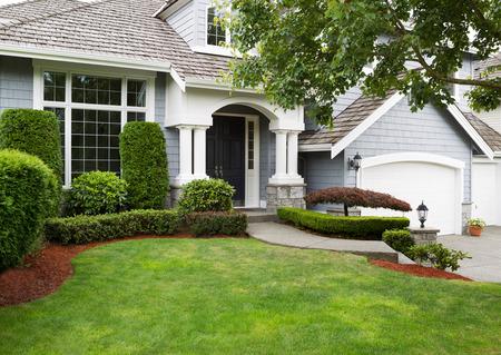Nieuw geschilderde buitenkant van een Noord-Amerikaanse huis in de zomer met groen gras en bloemperken Stockfoto