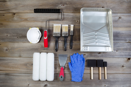 Overhead view of new painting accessories on rustic wood consisting of paint brushes, roller covers, pan, applicators, mask, latex gloves, scraper and hand roller frame Stock fotó