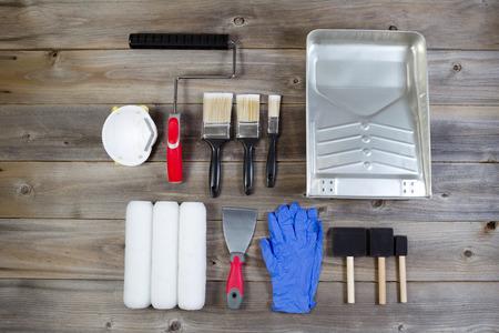 Vue aérienne de nouveaux accessoires de peinture sur bois rustique comprenant des pinceaux, rouleaux couvertures, pan, applicateurs, masque, gants en latex, grattoir et le cadre du rouleau à la main