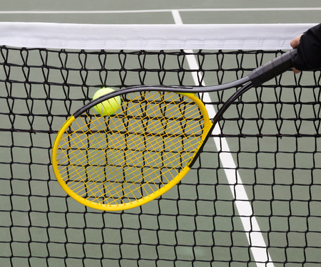 Tennis ball goes into net with racket and players hand behind ball