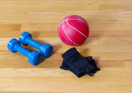 Workout gloves, dumbbells and weight ball lying on wooden gym floor  Stok Fotoğraf