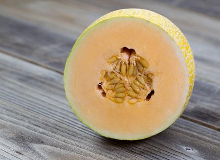 honeydew: Closeup view of a freshly cut half melon on rustic wood Stock Photo