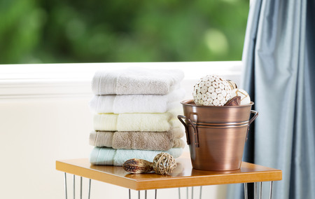 window treatments: Spa accessories on top of table with open windows showing blurred green trees in background
