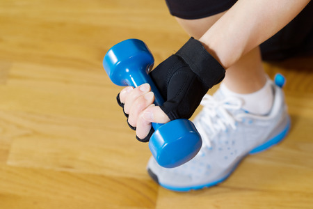 Horizontal image of female hand wearing workout glove while lifting small dumbbell weight with wooden gym floor in background