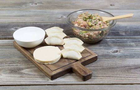 Horizontal photo of homemade traditional Chinese Dumplings being made from raw ingredients