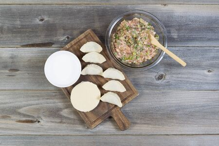 consist: Overhead view of raw ingredients used to make Chinese Dumplings. Items consist of raw pork, green onions, wrappers, spoon, bowl of water, and wooden server Stock Photo