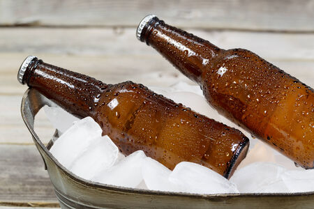 Closeup horizontal view of bottled beer in bucket of fresh real ice with dew on the outside Banco de Imagens - 29813013