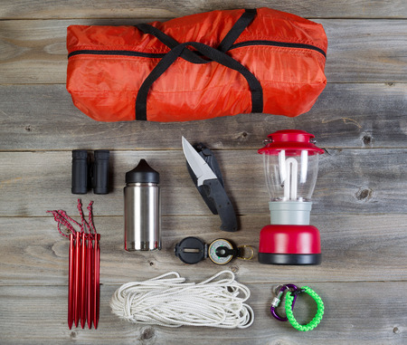 camping tent: Overhead view of basic hiking gear placed on weathered wooden boards. Items include tent inside of bag, pegs, compass, canteen, rope, knife, case, lantern and binoculars.  Stock Photo