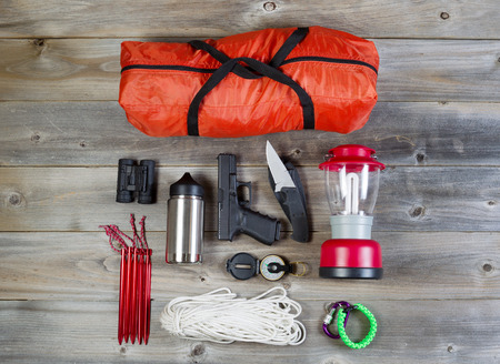 Overhead view of hiking gear and personal protection, pistol and knife, placed on rustic wood Stock Photo