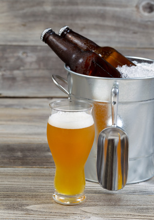 bottled beer: Vertical view of a freshly pour gold beer with bottled beer sitting inside metal bucket filled with crushed iced and rustic wood in background  Stock Photo