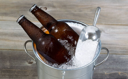condensate: Closeup top view of fresh bottled beer sitting inside metal bucket filled with crushed iced and rustic wood in background  Stock Photo