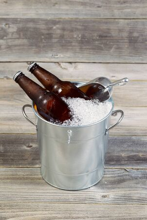 beer bucket: Vertical view of two unopened bottles of beer sitting inside metal bucket filled with crushed iced and rustic wood in background  Stock Photo
