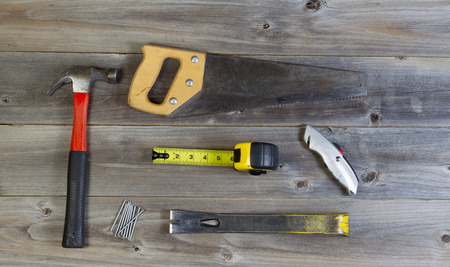 pry: Top view of basic home repair tools consisting of wood saw, hammer, nails, box cutter, pry bar and tape measure on rustic wooden boards