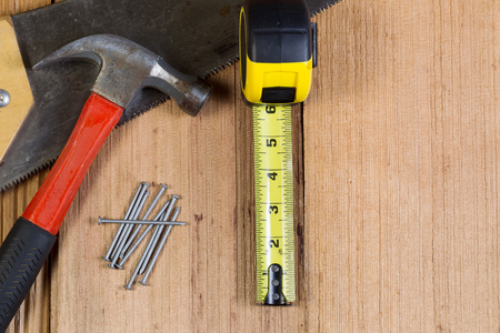cedar shakes: Top view of home repair tools consisting of wood saw, hammer, nails, and tape measure on cedar wooden shingles for roof Stock Photo