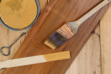 Closeup top view of painting tools consisting of hand brush, stir stick, can opener, and paint lid on cedar wooden shingles with top board stained and unstained boards underneath