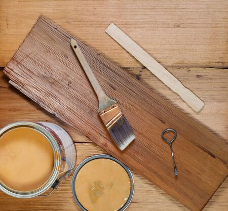 Closeup top view of painting tools consisting of hand brush, stir stick, can opener, paint lid and full can on cedar wooden shingles with top board stained and unstained boards underneath  Stock Photo