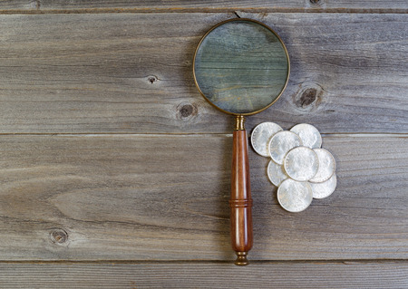 coin silver: Horizontal view of an antique round shaped magnifying glass and a pile of old silver dollar coins on rustic wood