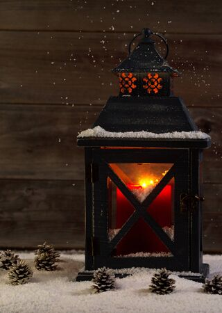 old barn in winter: Vertical front view of an old lantern with glowing red candle inside surrounded by snow and rustic wood