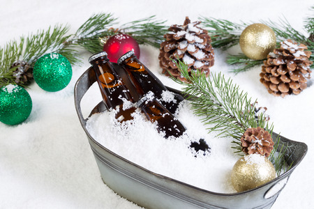 beer bucket: Closeup horizontal view of bottled beer, placed in a vintage metal bucket, surrounded by white snow and Christmas ornaments