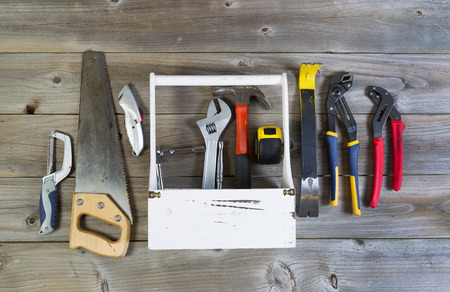 home repair: Over head view of basic home repair tools and holder on rustic wooden boards