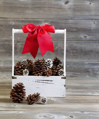 Vertical front view of a wooden hand holder filled with pine cones and large red bow for Christmas season on rustic wood