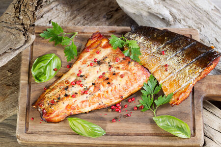 Closeup horizontal view of smoked salmon fillets with seasoning inside of drift wood on serving board photo