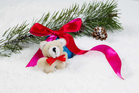 stuffed animals: Closeup front view of small fur bear with snow covered fir branch, red ribbon and pine cones in background