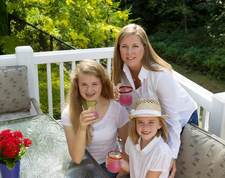 Top front view of happy mother and daughters, looking forward, drinking grapefruit juice while outdoors on patio with woods in background  photo