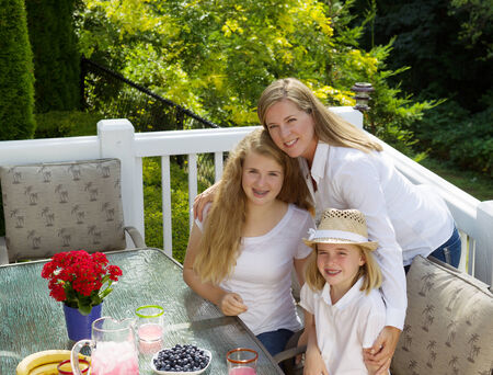 Front view of mature mother holding her two happy daughters while eating breakfast outdoors, during summer time, on patio with woods in background  photo