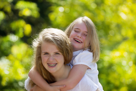 Front forward view, with focus on older sister, of oldest sister holding younger sister on her back while laughing together Stock fotó