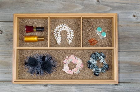 storage: Top view of storage drawer with woman accessories consisting of ear rings, pearl necklace, hair scrunchies, and nail polish