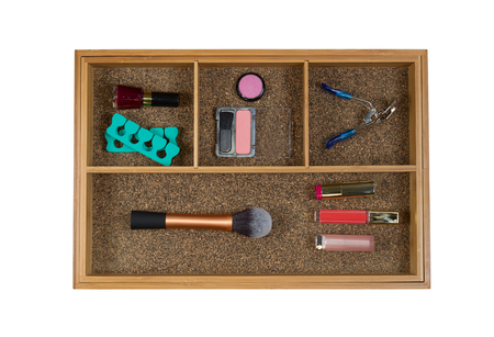 lip stick: Top view of storage drawer with woman accessories consisting blush, brush, eye lash curler, lip stick, and nail polish isolated on white